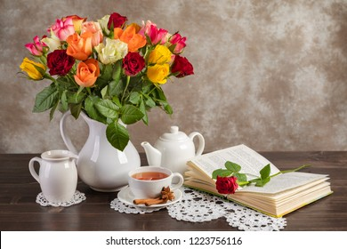 Still life roses, tea and a book on the table.