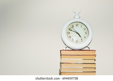 Still life round clock on stack of books. Education and learning concept. Invest time in studies. Time to upgrade ideas. Increase knowledge. Back to school. Copy space for text. Time read more