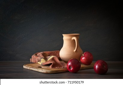 Still life in a rustic style. Red apples and clay jug on a wooden table.