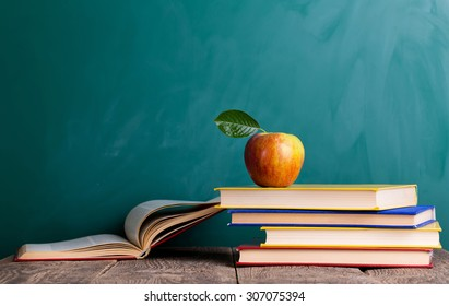 """Still life with school books and apple against blackboard with """"back to school"""" on background"""