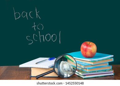 Still life with school supplies. Blackboard in chalk chalkboard. Green background. Notebooks, notebooks, felt-tip pens, colored pencils. Colorful picture. Beginning of the school year. Copy space.