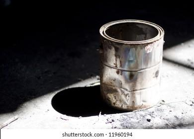 Still life shot of a rusty old paint bucket under dramatic lighting.
