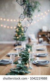 Still life shot of table setting and decoration prepared for a family dinner, christmas celebration at home, christmas tree on background.
