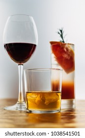 Still life shot of a whiskey glass on foreground and glass of red wine, paloma cocktail on background