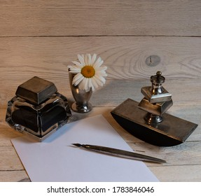 Still life from a silver writing set: inkwell, paperweight, pen, stamp and chamomile in a glass.