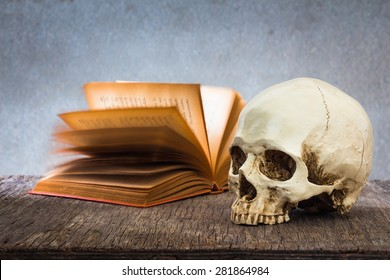 Still life with skull and old book on wooden table over grunge background