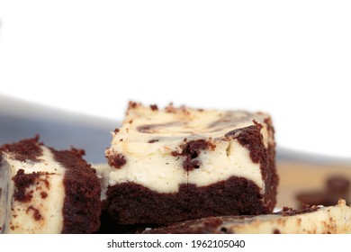 Still life with a slice of cheesecake brownie. The background is white. Close-up.