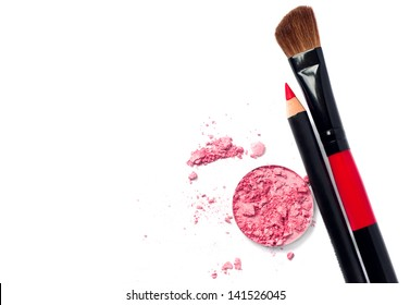 Still life of a small makeup kit light tender pink eyeshadow, red lip pencil, special professional brush for eye shadow applying. Isolated on white background, copy space