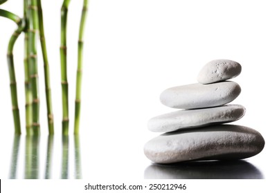 Still life of spa stones on glossy surface isolated on white