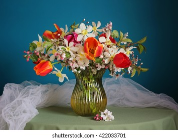 Still life with spring around the bouquet of daffodils, tulips, flowering branches of Apple and cherry in a glass vase on round table on a blue background.