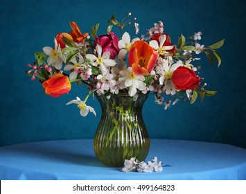 Still life with spring flowers on a blue background. Bouquet with daffodils, tulips and branches of the cherry blossoms.
