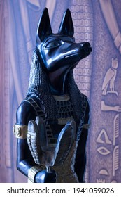 Still life of statue of mythology jackal anubis inpu anup. In the background are Egyptian motifs with hieroglyphs.