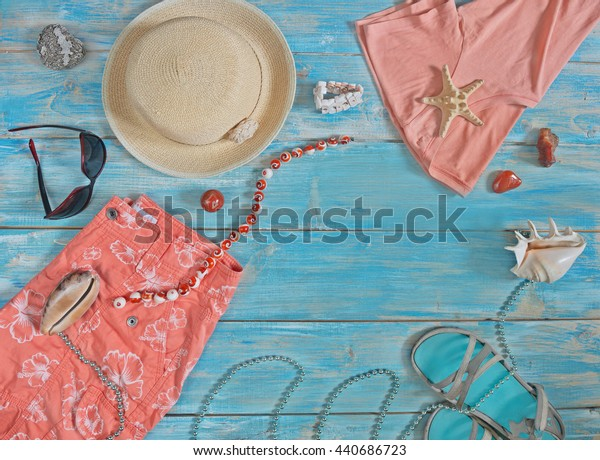 Still life in  style of flat lay of subjects beachwear coral colors spread out against blue background.