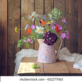 Still life with summer bouquet in a jar on the table in the background of the boards.