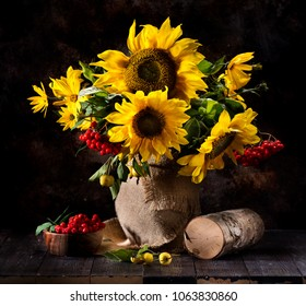 Still life with sunflowers, yellow flowers and rowan berries in a vase