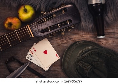 Still life symbolising vagabond lifestyle, with a guitar, playing cards, old clothes, alcohol and knife