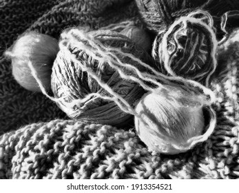 Still life of tangles, woolen and acrylic threads, knitting needles, knitted products. Soft light from the window. Knitting as a hobby. Manufacturing of fashionable warm clothes. Monochrome image