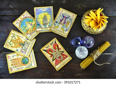 Still life with the tarot cards, magic stones and candles on wooden table. Fortune telling seance or black magic ritual. Scary still life with occult and esoteric symbols. Halloween or divination rite