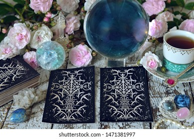Still life with tarot cards, white roses and crystal ball.   Esoteric, wicca and occult background, fortune telling and divination ritual with tarot cards.