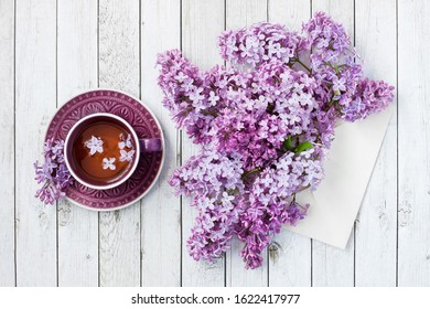 Still life with tea cup and lilac on wooden background