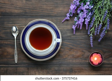 Still life with tea cup on saucer, lavender, silver tea spoon and aroma candle. Top view.