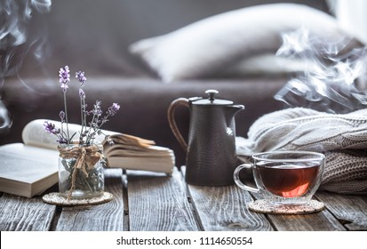 still life tea drinking in the living room a cup of tea with a kettle and a book on a wooden table, the concept of coziness