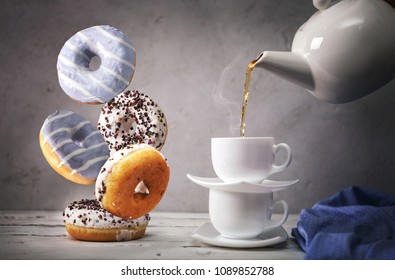 Still life with tea and falling down donuts
