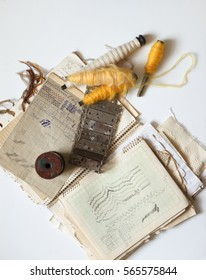 Still life of textile manufactory. Spools of thread, sketches, textile patterns, shuttles