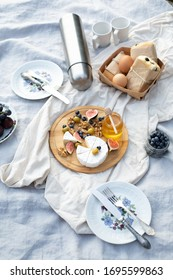 Still life of thermos flask, ciabatta sandwich, eggs, cheese plate, ripe fruit on tablecloth with wool cover and pillow. Appetizing food served on gray linen tablecloth for autumn picnic in open air.