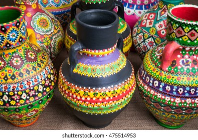 Still life of three artistic painted colorful handcrafted pottery vases on on sackcloth background