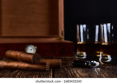 Still life with three cuban cigars, two glasses of whiskey or rum, lighter and wooden box with hygrometer. Old wooden table top and black background. Space for your text.