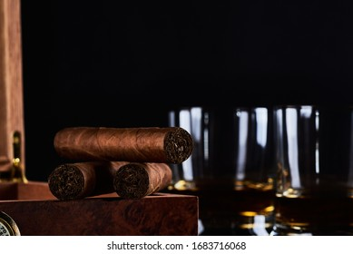 Still life with three cuban cigars, two glasses of whiskey or rum and wooden box with hygrometer and black background. Space for your text. - Shutterstock ID 1683716068