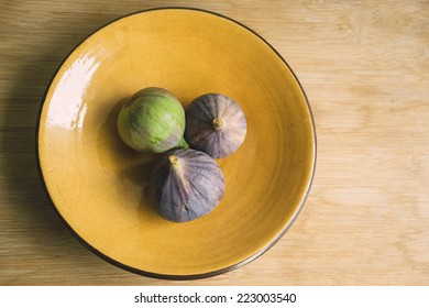 Still life of three figs on yellow plate