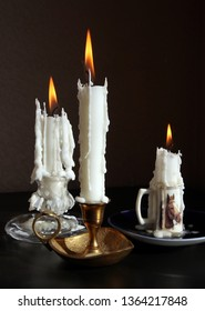 Still life with three vintage candlesticks with burning candles against low key background. Selective and soft focus.