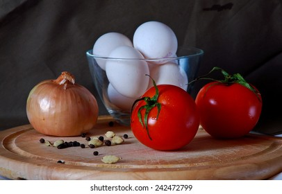 Still life with a tomatoes, onion, eggs and spices
