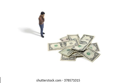 Still Life of a Toy Person Standing Next to a Pile of Money on a White Background