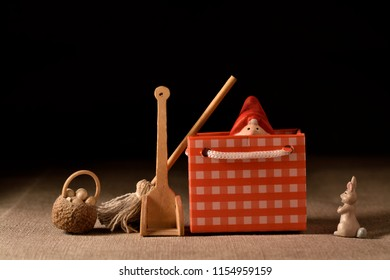 still life with toys gift bag broom shovel rabbit and food basket