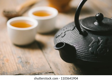 Still life with traditional asian herbal tea prepared in vintage cast iron teapot with organic dry herbs on rustic wooden table. Healthy green tea in tea cups closeup. Japanese cuisine.