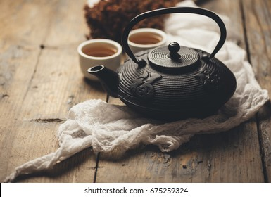 Still life with traditional asian herbal tea prepared in vintage cast iron teapot with organic dry herbs on rustic wooden table. Retro filter.