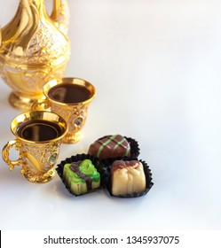Still life with traditional golden arabic coffee set with dallah, cup and chocolate candy. White background. Selective focus. Copy space.