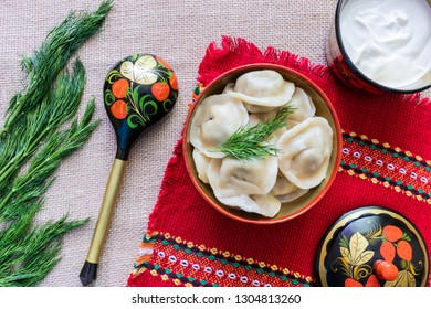 Still life with traditional Russian wooden utensils and the main national dish - pelmeni (dumplings).