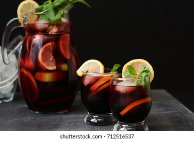 Still life of traditional Spanish wine beverage sangria with strawberries, orange and ice on a table. Selective focus.