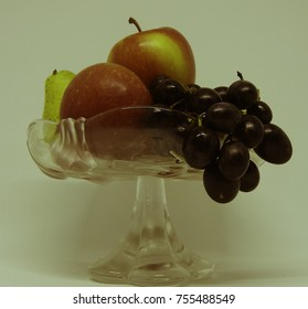 Still life, a transparent vase with apples, grapes and pear, old style photo