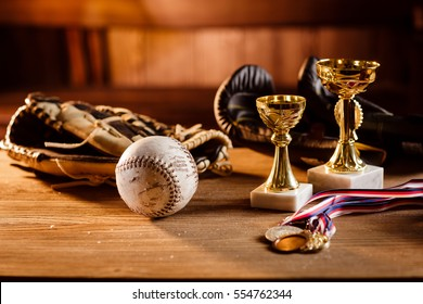 Still life of trophy, medals, vintage boxing gloves,  grunge baseball gloves with white ball over wooden table and dark background, with warm shiny lights in front of wooden background.
