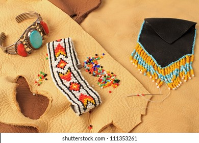 Still life with turquoise and silver wrist band, beaded bracelet and Indian Wampum Bag on assorted scraps of leather and buckskin.