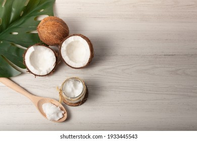 Still life of two coconuts, one of them cut in half, with a jar of coconut oil and a wooden spoon with space on the right for text