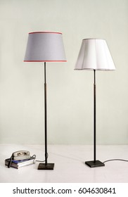 Still Life of Two Floor Lamps - One with Gray Shade and One with White Shade - with Stack of Books and Telephone in Room with Plain Background