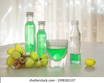 Still life with two full and one open small bottles of mint liqueur, glass of liqueur, green grapes, half a walnut on white table,shot with backlight from the sunlit window,selective focus