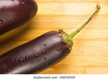 still life - two healthy and delicious purple eggplants on wooden Board