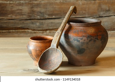 Still life with two pots and a wooden spoon.